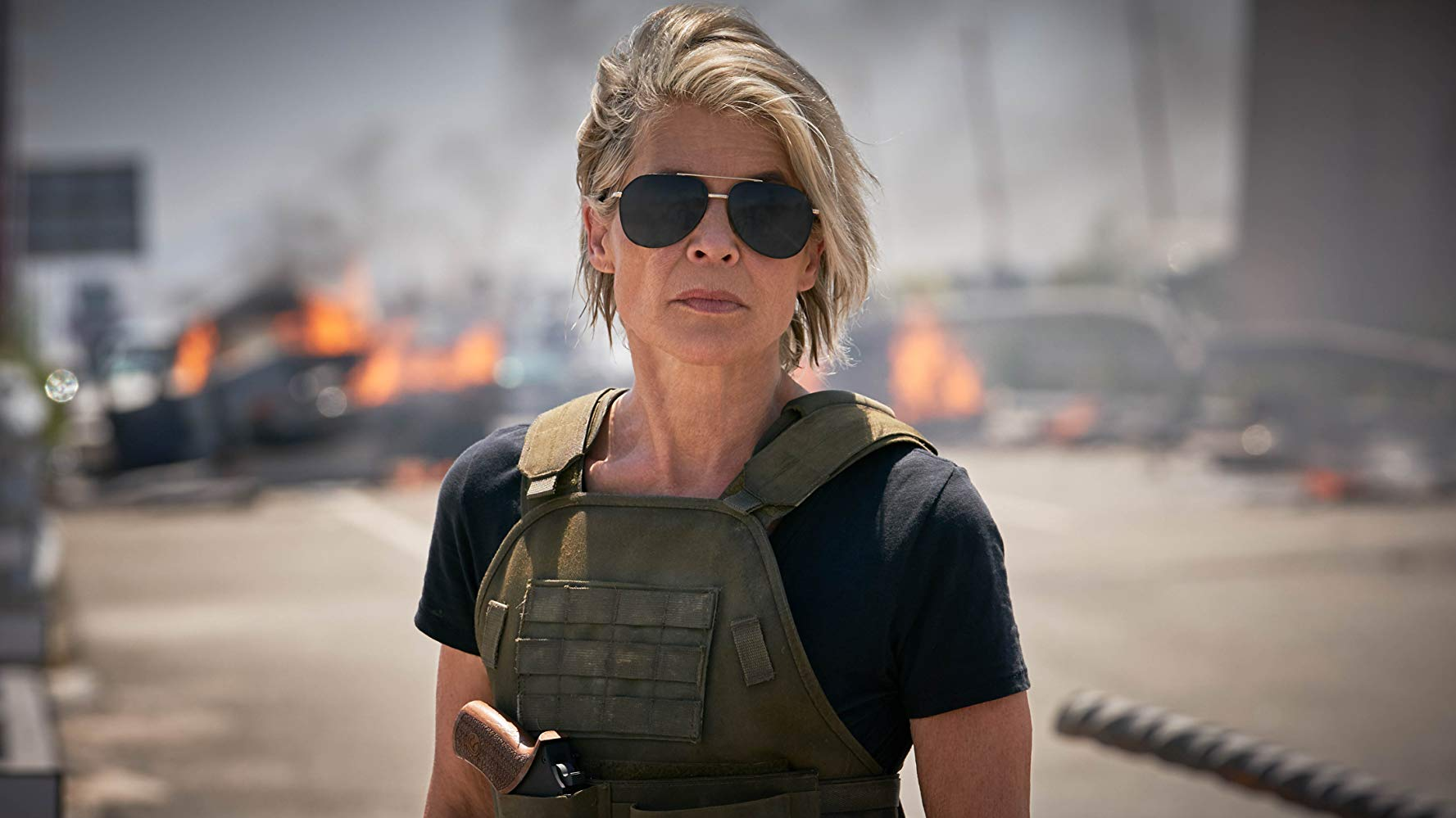 Sarah Conner wearing sunglasses and a kevlar vest stares menacingly at the camera.