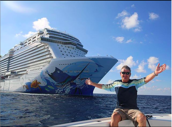 Guy Harvey in front of a cruise ship decorated with his artwork.