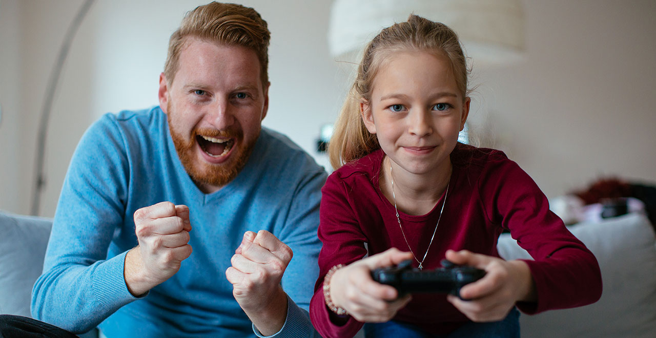 dad playing video game with daughter