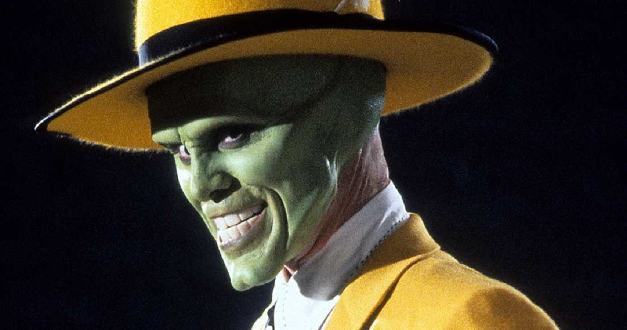 Carrey grinning maniacally with a yellow fedora and behind his iconic green mask