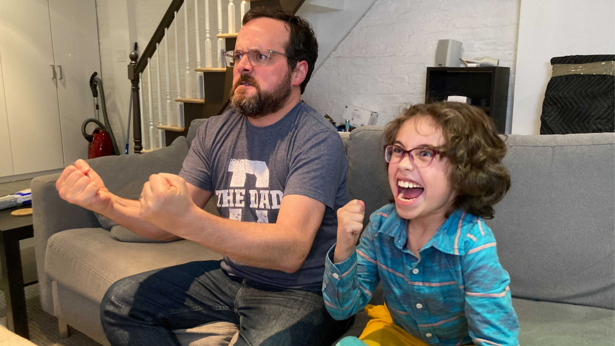 a man and his son cheer in excitement while playing a video game.