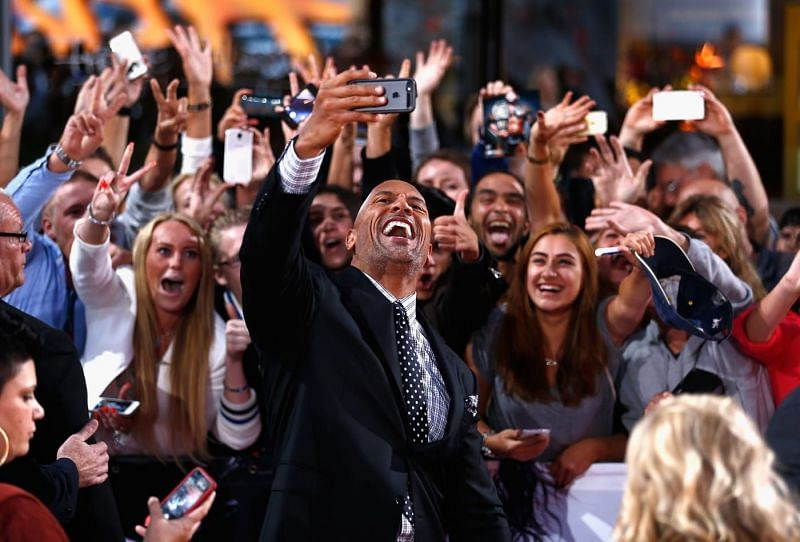 The Rock takes selfies with fans on the red carpet.