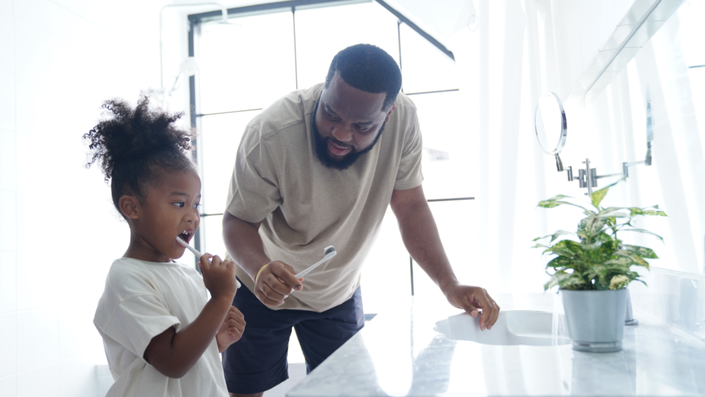 Father and daughter doing brushing in bathroom