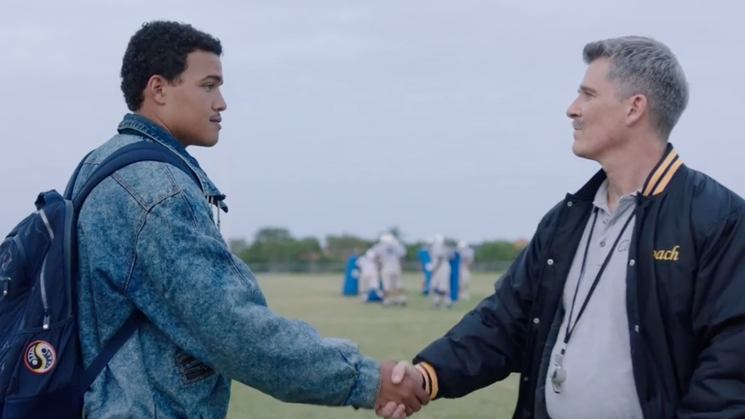 A scene from The Rock's new show where young Dwayne Johnson shakes his coaches hand.