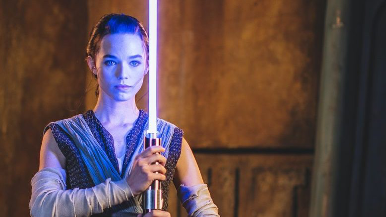 Rey holding a new Disney lightsaber