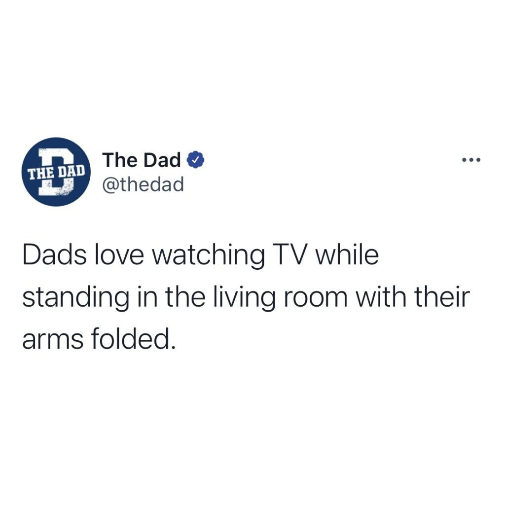 Dads love watching TV while standing in the living room with their arms folded.