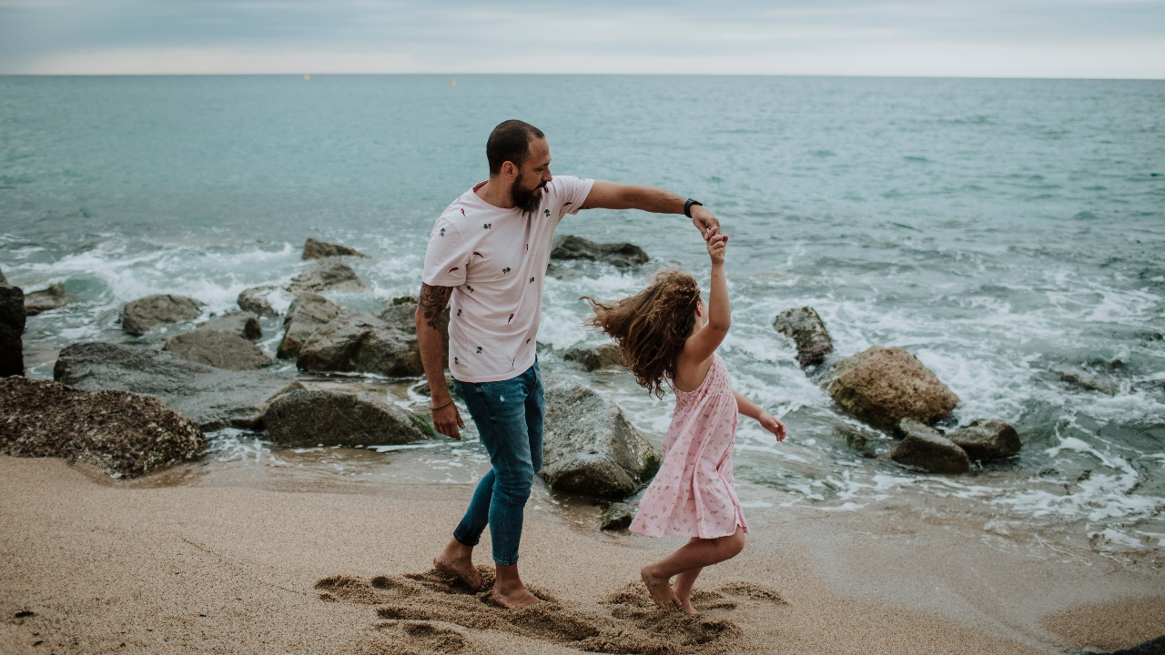 dad and daughter songs, father dancing with daughter on the beach